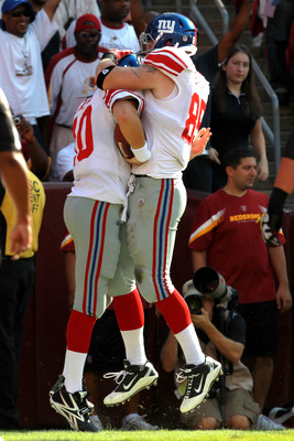 LANDOVER, MD - SEPTEMBER 11:  (L-R) Quarterback  Eli Manning #10 of the New York Giants celebrates with teammate Jake Ballard #85 after scoring on a two-yard touchdown run in the first quarter against the Washington Redskins at FedExField on September 11,