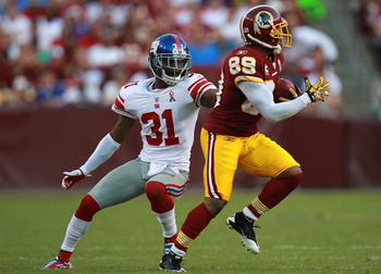 LANDOVER, MD - SEPTEMBER 11:   Santana Moss #89 of the Washington Redskins runs the ball past  Aaron Ross #31 of the New York Giants during the season opener at FedExField on September 11, 2011 in Landover, Maryland.  (Photo by Ronald Martinez/Getty Image