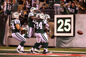 EAST RUTHERFORD, NJ - SEPTEMBER 11:  Nick Bellore #54, Emanuel Cook #27 and Marquice Cole #34 of the New York Jets jump on teammate Isaiah Trufant #35 after he returned a blocked punt 18-yards for a touchdown in the fourth quarter against the Dallas Cowbo