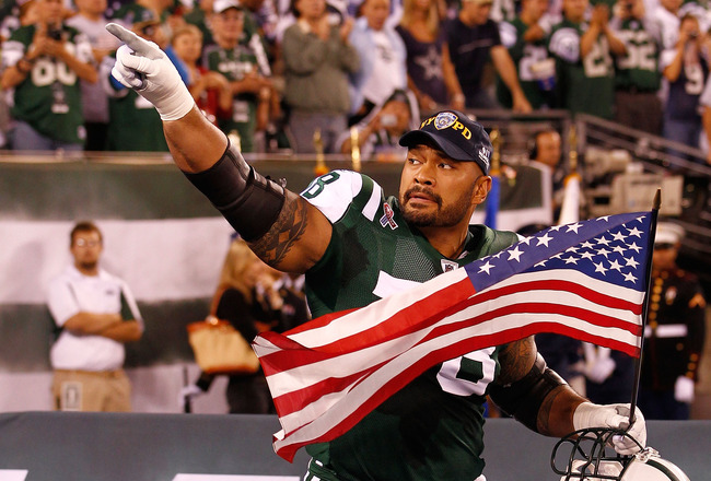 EAST RUTHERFORD, NJ - SEPTEMBER 11:  Wayne Hunter #78 of the New York Jets runs with an American Flag on to the field during pregame festivities against the Dallas Cowboys during their NFL Season Opening Game at MetLife Stadium on September 11, 2011 in Ea