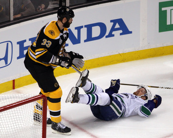 BOSTON, MA - JUNE 13:  Henrik Sedin #33 of the Vancouver Canucks gets knocked to the ice after being checked by Zdeno Chara #33 of the Boston Bruins during Game Six of the 2011 NHL Stanley Cup Final at TD Garden on June 13, 2011 in Boston, Massachusetts.