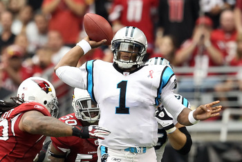 GLENDALE, AZ - SEPTEMBER 11:  Quarterback Cam Newton #1 of the Carolina Panthers throws a pass under pressure from Darnell Dockett #90 of the Arizona Cardinals during the NFL season opening game at the University of Phoenix Stadium on September 11, 2011 i