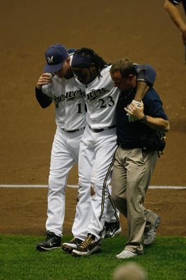 MILWAUKEE, WI - JULY 27: Rickie Weeks #23 of the Milwaukee Brewers is carried off the field by Ron Roenicke and a trainer after an injury against the Chicago Cubs at Miller Park on July 27, 2011 in Milwaukee, Wisconsin.  The Brewers defeated the Cubs 2-0.