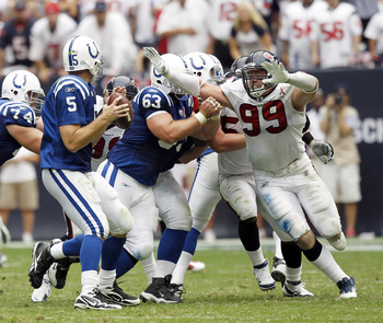 HOUSTON - SEPTEMBER 11:  Quarterback Kerry Collins #5 of the Indianapolis Colts prepares to pass as defensive end J.J. Watt #99 of the Houston Texans applies pressure on center Jeff Saturday #63 during the season-opening game at Reliant Stadium on Septemb