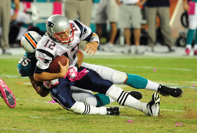 MIAMI - OCTOBER 4: Tom Brady #12 of the New England Patriots is sacked by Koa Misi #55 of the Miami Dolphins at Sun Life Field on October 4, 2010 in Miami, Florida. (Photo by Scott Cunningham/Getty Images)