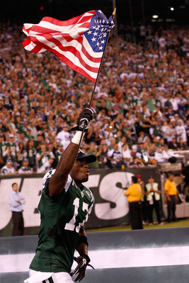 EAST RUTHERFORD, NJ - SEPTEMBER 11:  Plaxico Burress #17 of the New York Jets runs with an American Flag on to the field during pregame festivities against the Dallas Cowboys during their NFL Season Opening Game at MetLife Stadium on September 11, 2011 in