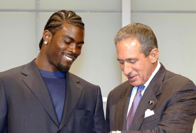 Atlanta Falcons quarterback Michael Vick and owner Arthur Blank compare watches and check the time before a 2005 American Bowl press conference at the Tokyo Dome Hotel in Japan, Thursday August 4, 2005.  (Photo by Al Messerschmidt/Getty Images)