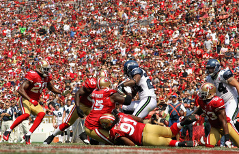 SAN FRANCISCO, CA - SEPTEMBER 11:  Marshawn Lynch #24 of the Seattle Seahawks is tackled by the San Francisco 49ers during their season opener at Candlestick Park on September 11, 2011 in San Francisco, California.  (Photo by Ezra Shaw/Getty Images)