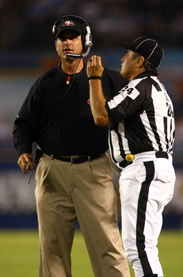 SAN DIEGO, CA - SEPTEMBER 1:  Head Coach Jim Harbaugh of the San Francisco 49ers speaks to Head Linesman Tom Stabile #24 on the field during their preseason NFL Game against  the San Diego Chargers on September 1, 2011 at Qualcomm Stadium in San DIego, Ca
