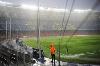 BARCELONA, SPAIN - MAY 03:  A steward stands on the pitch under heavy rain prior to the UEFA Champions League Semi Final second leg match between Barcelona and Real Madrid at the Nou Camp on May 3, 2011 in Barcelona, Spain.  (Photo by David Ramos/Getty Im