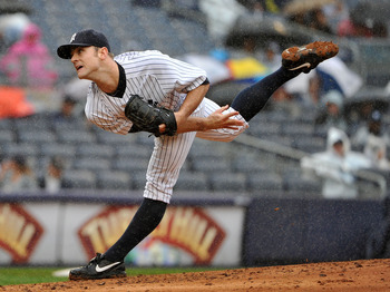 NEW YORK, NY - SEPTEMBER 07: David Robertson #30 of the New York Yankees throws a pitch in the rain during the top of the eighth inning against the Baltimore Orioles and New York Yankees on September 7, 2011 at Yankee Stadium in the Bronx borough of New Y