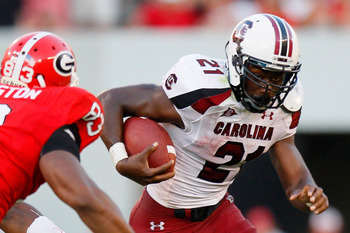 ATHENS, GA - SEPTEMBER 10:  Marcus Lattimore #21 of the South Carolina Gamecocks rushes upfield against Cornelius Washington #83 of the Georgia Bulldogs at Sanford Stadium on September 10, 2011 in Athens, Georgia.  (Photo by Kevin C. Cox/Getty Images)