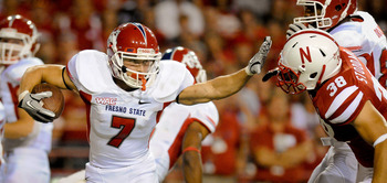 LINCOLN, NE - SEPTEMBER 10: Devon Wylie #7 of the Fresno State Bulldogs stiff arms Graham Stoddard #38 of the Nebraska Cornhuskers during their game at Memorial Stadium September 10, 2011 in Lincoln, Nebraska. Nebraska won 42-29.(Photo by Eric Francis/Get