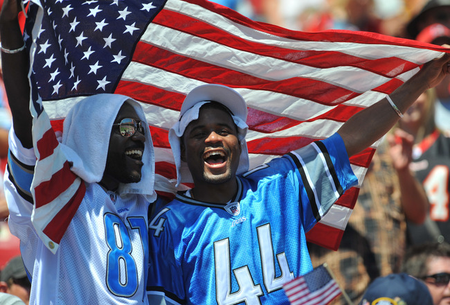 TAMPA, FL - SEPTEMBER 11:  Two Detroit Lions fans stand under an American Flag during the season opener against the Tampa Bay Buccaneers at Raymond James Stadium September 11, 2011 in Tampa, Florida. (Photo by Al Messerschmidt/Getty Images)