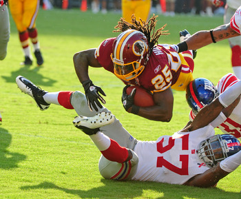 LANDOVER, MD - SEPTEMBER 11: Tim Hightower #25 of the Washington Redskins carries the ball against Jacquain Williams #57 of the New York Giants season-opening game at FedEx Field on September 11, 2011 in Landover, Maryland. (Photo by Scott Cunningham/Gett