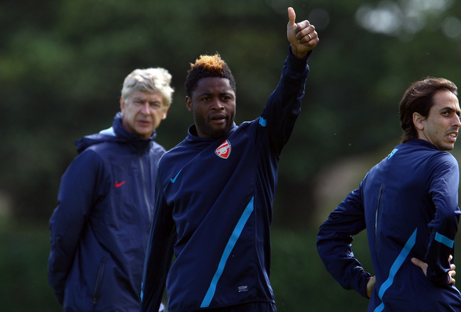 ST ALBANS, ENGLAND - SEPTEMBER 12:  A thumbs up from Alex Song of Arsenal as Yossi Benayoun and Arsene Wenger look on during a training session ahead of their UEFA Champions League Group match against Borussia Dortmund, London Colney on September 12, 2011
