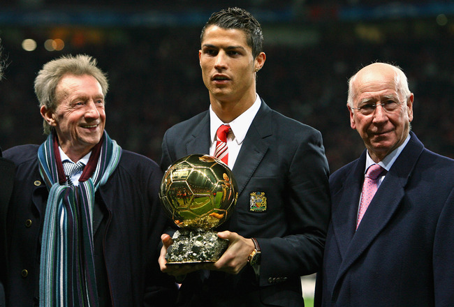 MANCHESTER, UNITED KINGDOM - DECEMBER 10:  Cristiano Ronaldo (C) of Manchester United receives the Ballon d'or as the European Footballer of the Year flanked by previous winners Denis Law (L) and Bobby Charlton before the UEFA Champions League Group E mat