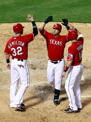 ARLINGTON, TX - AUGUST 22: Josh Hamilton #32 and Michael Young #10 celebrate with Mike Napoli #25 of the Texas Rangers after Napoli hit a three-run home run against the Boston Red Sox at Rangers Ballpark in Arlington on August 22, 2011 in Arlington, Texas