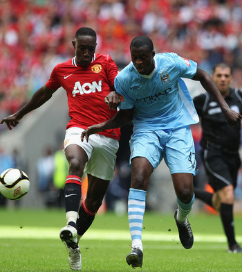LONDON, ENGLAND - AUGUST 07:  Danny Welbeck of Manchester United and Yaya Toure of Manchester City battle for the ball during the FA Community Shield match sponsored by McDonald's between Manchester City and Manchester United at Wembley Stadium on August