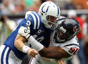 HOUSTON - SEPTEMBER 12:  Quarterback Peyton Manning #18 of the Indianapolis Colts is tackled by Mario Williams #90 of the Houston Texans during the NFL season opener at Reliant Stadium on September 12, 2010 in Houston, Texas.  (Photo by Ronald Martinez/Ge