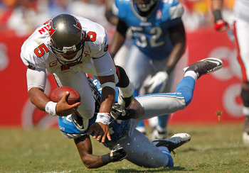 TAMPA, FL - SEPTEMBER 11:  Josh Freeman #5 of the Tampa Bay Buccaneers is tackled by  Amari Spievey #42 of the Detroit Lions during the season opener  at Raymond James Stadium on September 11, 2011 in Tampa, Florida.  (Photo by Mike Ehrmann/Getty Images)