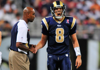 ST. LOUIS, MO - SEPTEMBER 11: Sam Bradford #8 of the St. Louis Rams reacts as the trainer checks his hand during a game against the Philadelphia Eagles at the Edward Jones Dome on September 11, 2011 in St. Louis, Missouri. The Eagles defeated the Rams 31-