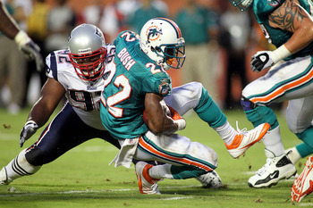 MIAMI GARDENS, FL - SEPTEMBER 12:  Defensive end Albert Haynesworth #92 of the New England Patriots tackles Running back Reggie Bush #22 of the Miami Dolphins at Sun Life Stadium on September 12, 2011 in Miami Gardens, Florida.  (Photo by Marc Serota/Gett