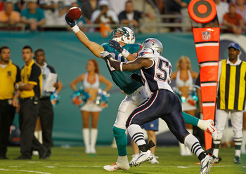 MIAMI GARDENS, FL - SEPTEMBER 12:   Anthony Fasano #80 of the Miami Dolphins makes a catch over  Gary Guyton #59 of the New England Patriots during a game  at Sun Life Stadium on September 12, 2011 in Miami Gardens, Florida.  (Photo by Mike Ehrmann/Getty