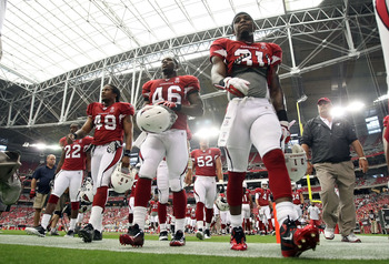 GLENDALE, AZ - SEPTEMBER 11:  (L-R) Crezdon Butler #22, Rashad Johnson #49, Alfonso Smith #46 and Richard Marshall #31 of the Arizona Cardinals walk off the field during the NFL season opening game against the Carolina Panthers at the University of Phoeni