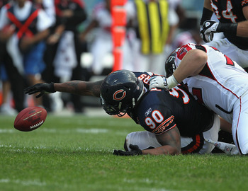 CHICAGO, IL - SEPTEMBER 11:  Julius Peppers #90 of the Chicago Bears reaches for a fumbled ball as Sam Baker #72 of the Atlanta Falcons flls on his back at Soldier Field on September 11, 2011 in Chicago, Illinois. The Bears defeated the Falcons 30-12.  (P
