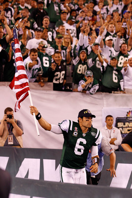 EAST RUTHERFORD, NJ - SEPTEMBER 11:  Mark Sanchez #6 of the New York Jets runs with an American Flag on to the field during pregame festivities against the Dallas Cowboys during their NFL Season Opening Game at MetLife Stadium on September 11, 2011 in Eas