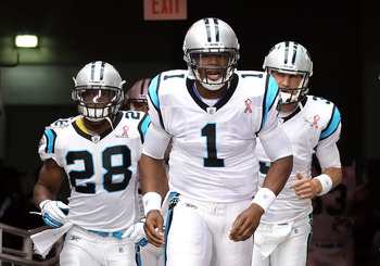 GLENDALE, AZ - SEPTEMBER 11:  Quarterback Cam Newton #1 of the Carolina Panthers leads teammates Jonathan Stewart #28 (L) and Derek Anderson #3 (R) out onto the field before the NFL season opener game against the Arizona Cardinals at the University of Pho