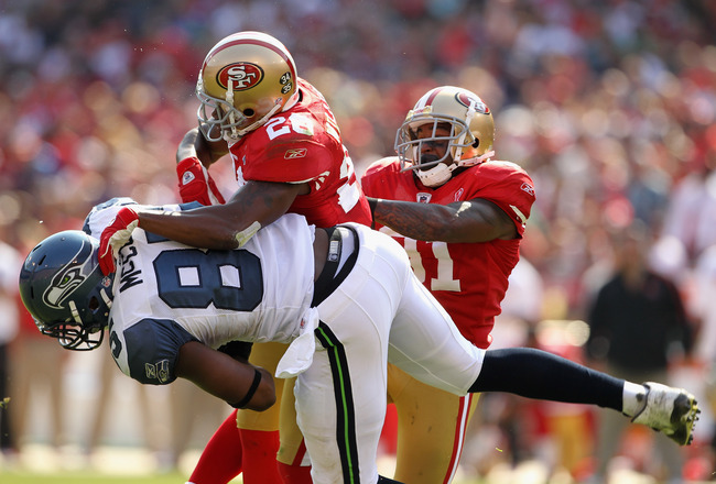 SAN FRANCISCO, CA - SEPTEMBER 11:  Anthony McCoy #85 of the Seattle Seahawks is hit by Madieu Williams #20 and Donte Whitner #31 of the San Francisco 49ers during their season opener at Candlestick Park on September 11, 2011 in San Francisco, California.