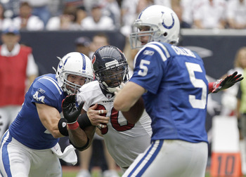 HOUSTON, TX - SEPTEMBER 11: Quarterback Kerry Collins #5 of the Indianapolis Colts is blind sighted by linebacker Mario Williams #90 of the Houston Texans on September 11, 2011 at Reliant Stadium in Houston, Texas. Texans won 34 to 7.(Photo by Thomas B. S