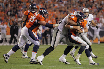 DENVER, CO - SEPTEMBER 12:  Quarterback Kyle Orton #8 of the Denver Broncos is sacked by defensive tackle  Richard Seymour #92 of the Oakland Raiders in the third quarterat Sports Authority Field at Mile High on September 12, 2011 in Denver, Colorado. The