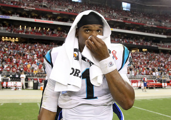 GLENDALE, AZ - SEPTEMBER 11:  Quarterback Cam Newton #1 of the Carolina Panthers reacts as he walks off the field following the NFL season opening game against the Arizona Cardinals at the University of Phoenix Stadium on September 11, 2011 in Glendale, A