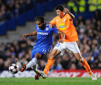 LONDON, ENGLAND - DECEMBER 08:  Florent Malouda of Chelsea  holds off Helio Pinto of APOEL Nicosia during the UEFA Champions League Group D match between Chelsea and Apoel Nicosia at Stamford Bridge on December 8, 2009 in London, England.  (Photo by Jamie