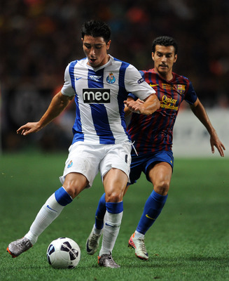 MONACO - AUGUST 26: Jorge Fucile (L) of FC Porto shields Pedro Rodriguez of FC Barcelona from the ball during the UEFA Super Cup match between FC Barcelona and FC Porto at Louis II Stadium on August 26, 2011 in Monaco, Monaco.  (Photo by Jasper Juinen/Get