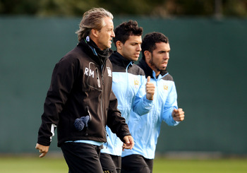 MANCHESTER, ENGLAND - SEPTEMBER 13:  Manchester City manager Roberto Mancini with Carlos Tevez (R) and Sergio Auero during a training session at Carrington Training Ground on September 13, 2011 in Manchester, England.  (Photo by Scott Heavey/Getty Images)