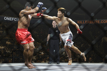 SINGAPORE - SEPTEMBER 03:A Sol Kwon (R) punches Eduard Folayang (L) during the ONE Fighting Championships lightweight bout  at Singapore Indoor Stadium on September 3, 2011 in Singapore.  (Photo by Suhaimi Abdullah/Getty Images)