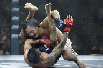 SINGAPORE - SEPTEMBER 03:  Leandro Issa (bottom) defends himself against  Soo Chui Kim (top) during the ONE Fighting Championships bantamweight bout at Singapore Indoor Stadium on September 3, 2011 in Singapore.  (Photo by Suhaimi Abdullah/Getty Images)