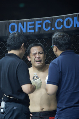 SINGAPORE - SEPTEMBER 03: Andy Wang (C) gets treatment for his eye injury during his fight against Zorobabel Moreira during the ONE Fighting Championships welterweight  bout  at Singapore Indoor Stadium on September 3, 2011 in Singapore.  (Photo by Suhaim