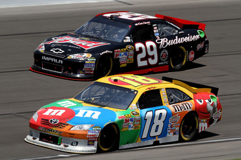 KANSAS CITY, KS - JUNE 05:  Kyle Busch, driver of the #18 M&M's Toyota, races Kevin Harvick, driver of the #29 Budweiser Chevrolet, during the NASCAR Sprint Cup Series STP 400 at Kansas Speedway on June 5, 2011 in Kansas City, Kansas.  (Photo by Jerry Mar