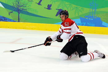 VANCOUVER, BC - FEBRUARY 26:  Ryan Getzlaf #51 of Canada reaches for the puck during the ice hockey men's semifinal game between the Canada and Slovakia on day 15 of the Vancouver 2010 Winter Olympics at Canada Hockey Place on February 26, 2010 in Vancouv
