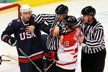 VANCOUVER, BC - FEBRUARY 28:  The Officials break up a scuffle between Jack Johnson #3 of the United States and Michael Richards #18 of Canada during the ice hockey men's gold medal game between USA and Canada on day 17 of the Vancouver 2010 Winter Olympi
