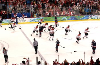 VANCOUVER, BC - FEBRUARY 28:  Members of Team Canada skate  from the bench area toward teammate Sidney Crosby #87 (not in photo) in the corner to celebrate their 3-2 overtime victory after the ice hockey men's gold medal game between USA and Canada on day