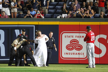 ATLANTA, GA - JULY 16: Jason Werth #28 of the Washington Nationals watches as security guards escort a fan in a wedding dress off of the field during the game against the Atlanta Braves on July 16, 2011 at Turner Field in Atlanta, Georgia. (Photo by Danie