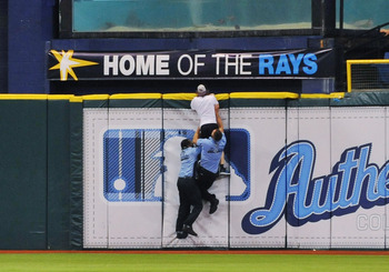 ST. PETERSBURG, FL - AUGUST 10:  Security chases a fan of the Tampa Bay Rays as he runs onto the field then jumps the centerfield wall in the ninth inning of their game against the Kansas City Royals August 10, 2011 at Tropicana Field in St. Petersburg, F