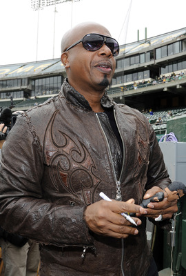 OAKLAND, CA - JULY 17: American rapper, entertainer MC Hammer signs a replica bobblehead doll of himself for a fan before a MLB baseball game between the Los Angeles Angels of Anaheim and the Oakland Athletics at the O.co Coliseum July 17, 2011 in Oakland