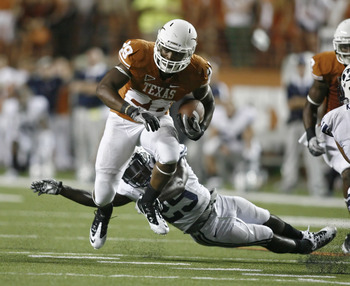 AUSTIN, TX - SEPTEMBER 10:  Running back Malcolm Brown #28 of the Texas Longhorns gets past defensive back Skye PoVey #29 of the BYU Cougars on September 10, 2011 at Darrell K. Royal-Texas Memorial Stadium in Austin, Texas.  Texas defeated BYU 17-16.  (Ph